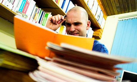 Male teacher marking books